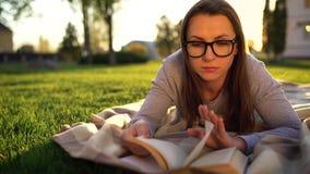 Menina no livro de leitura dos vidros que encontra-se para baixo em uma cobertura no parque no por do sol video estoque