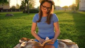 Menina no livro de leitura dos vidros que senta-se em uma cobertura no parque no por do sol filme