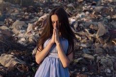 Menina no lixo a rezar no silêncio Imagem de Stock