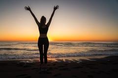 Menina no mar durante o por do sol Aptidão e estilo de vida saudável fotografia de stock royalty free