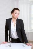 A menina no negócio veste a posição perto da tabela Imagens de Stock Royalty Free