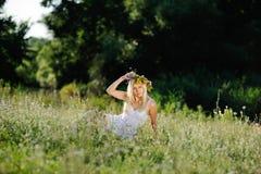 A menina no os sundress brancos e uma grinalda das flores em sua cabeça senta-se Fotografia de Stock Royalty Free