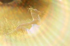 A menina no os sundress brancos e uma grinalda das flores em sua cabeça senta-se Imagem de Stock Royalty Free