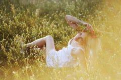 A menina no os sundress brancos e uma grinalda das flores em sua cabeça senta-se Imagens de Stock Royalty Free