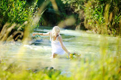A menina no os sundress brancos no rio começa uma grinalda das flores Fotos de Stock Royalty Free