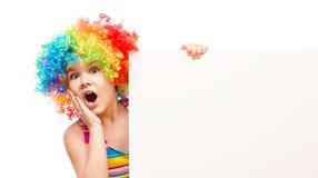 A menina no palhaço está guardando a bandeira vazia Fotos de Stock Royalty Free