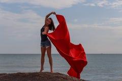 A menina no pano do vermelho do whith da praia foto de stock royalty free