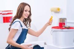A menina no papel masculino está pintando paredes Fotos de Stock
