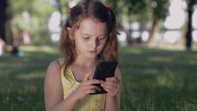 A menina no parque comunica-se com os amigos em redes sociais usando um smartphone Adolescente de sorriso no bate-papo usando o t vídeos de arquivo
