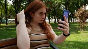 A menina no parque comunica-se nas redes sociais, dia ensolarado no banco video estoque