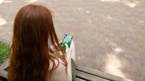 A menina no parque comunica-se nas redes sociais, dia ensolarado no banco vídeos de arquivo