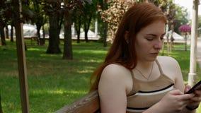 A menina no parque comunica-se nas redes sociais, dia ensolarado no banco filme