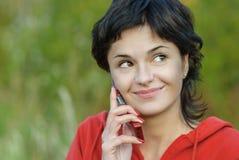 A menina no parque fala pelo telefone Fotografia de Stock