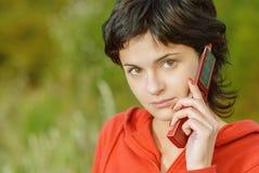 A menina no parque fala pelo telefone Foto de Stock