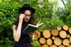 A menina no parque que lê um livro Fotografia de Stock Royalty Free