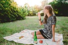 Menina no parque que olha a garrafa do champanhe imagem de stock