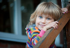 A menina no patamar da casa da vila Fotografia de Stock Royalty Free