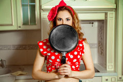 Menina no pino acima do estilo que levanta na cozinha com a frigideira no ha Fotos de Stock