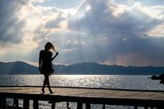 Menina no por do sol no cais Foto de Stock Royalty Free