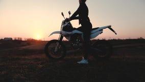Menina no por do sol que olha na distância ao sentar-se em uma motocicleta vídeos de arquivo