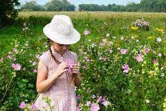 Menina no prado com flores Fotos de Stock