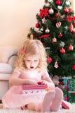 Menina no presente cor-de-rosa da abertura do vestido Fotos de Stock Royalty Free