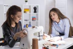 A menina no preto está costurando Seu colega está fazendo anotações imagem de stock
