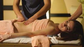 Menina no procedimento para uma massagem de quatro mãos no salão de beleza dos termas filme
