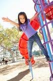 Menina no quadro de escalada no parque Imagens de Stock
