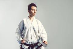 menina no quimono do terno do karaté no estúdio no fundo cinzento A criança fêmea mostra stans do judô ou do karaté no uniforme b Fotos de Stock