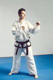 menina no quimono do terno do karaté no estúdio no fundo cinzento A criança fêmea mostra stans do judô ou do karaté no uniforme b Foto de Stock