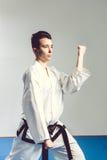 menina no quimono do terno do karaté no estúdio no fundo cinzento A criança fêmea mostra stans do judô ou do karaté no uniforme b Fotos de Stock Royalty Free
