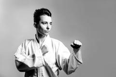 menina no quimono do terno do karaté no estúdio no fundo cinzento A criança fêmea mostra stans do judô ou do karaté no uniforme b Imagem de Stock