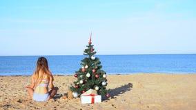Menina no recurso ao ano novo com uma árvore de Natal no mar vídeos de arquivo