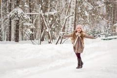 A menina no revestimento do inverno da manta corre felizmente em madeiras do inverno Imagens de Stock Royalty Free