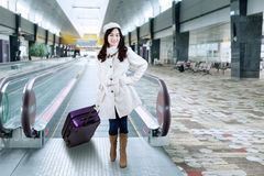 Menina no revestimento do inverno no corredor do aeroporto Fotos de Stock Royalty Free