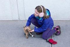 A menina no revestimento e na orelha da queda falha o agachamento para pet o yorkshire terrier minúsculo imagens de stock royalty free