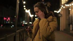 A menina no revestimento está estando na rua com luzes no fundo Focalizado no telefone, estabeleça seu cabelo video estoque