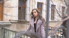 Menina no revestimento que levanta atrás da cerca na rua filme