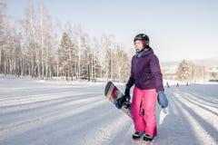 Menina no revestimento roxo e em calças cor-de-rosa com o snowboard nas mãos Fotos de Stock Royalty Free