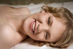 Menina no riso da cama Foto de Stock Royalty Free