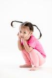 Menina no rosa com o penteado engraçado que senta-se no fundo branco Fotografia de Stock Royalty Free