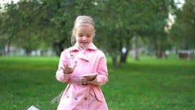 Menina no rosa que joga afastado notas de dólar em um parque filme
