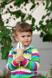 A menina no roupa colorida brilhante come o gelado Foto de Stock