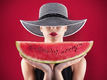 Menina no roupa de banho com melancia à disposição e fundo vermelho Fotos de Stock