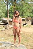Menina no roupa de banho na rocha Fotos de Stock Royalty Free