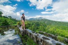 Menina no roupa de banho no hotel podre abandonado místico em Bali com céu azul indonésia Foto de Stock Royalty Free