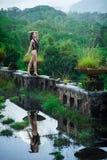 Menina no roupa de banho no hotel podre abandonado místico em Bali com céu azul indonésia Imagens de Stock