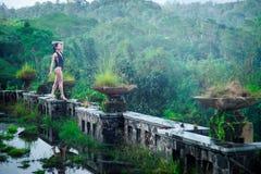 Menina no roupa de banho no hotel podre abandonado místico em Bali com céu azul indonésia Foto de Stock