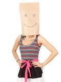 Menina no saco de papel ecológico de sorriso na cabeça fotografia de stock royalty free